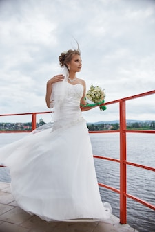 Bride with flowers in her hands standing in wind