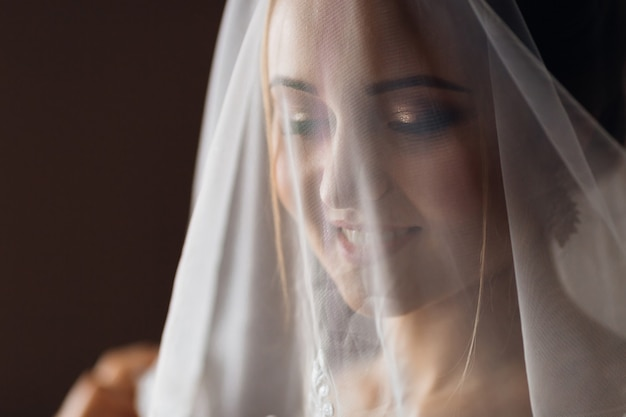 優しい化粧をした花嫁が結婚式のベールで顔を覆った。閉じる。
