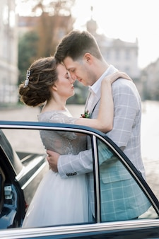 Bride with groom near old car. newlyweds kissing and embracing while standing behind old black retro car in old city center. lviv, ukraine