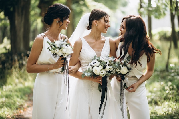 Bride with her bridesmaids in forest
