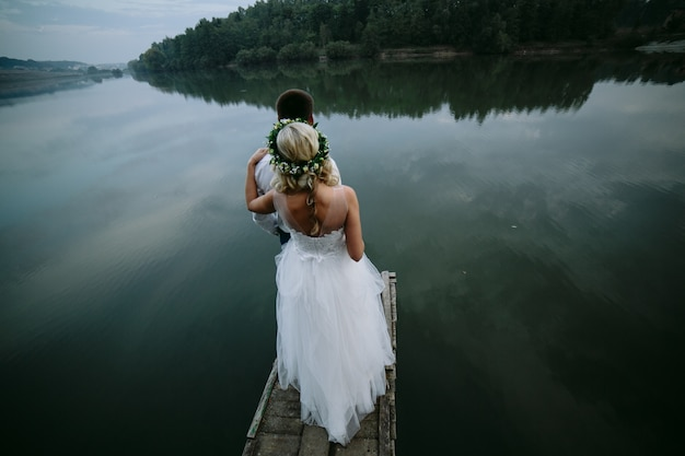 Bride with her husband in front looking at a lake