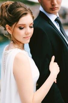 Невеста с высокой прической в белом платье держит за руку жениха в черном и белом пиджаке.