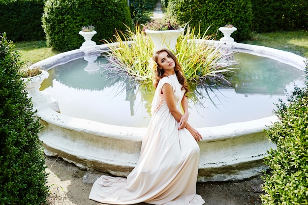 Bride with long curly hair in wedding dress sitting near fountain at park, wedding photo, portrait.