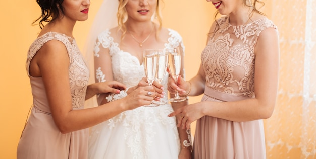 Bride with merry girlfriends at the wedding drink champagne from glasses. bride and girlfriends hug in the room. morning bride and girlfriends.