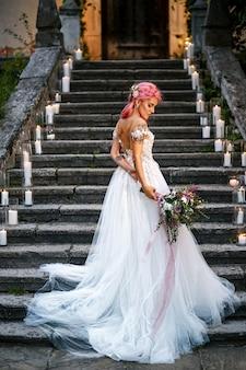 Невеста с розовыми волосами и татуировками на ее нежном плече стоит по стопам с блестящими свечами