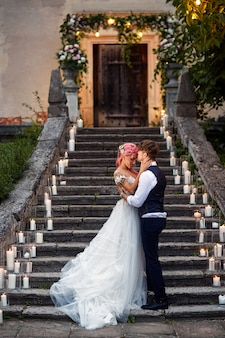 Bride with pink hair and stylish groom stand on footsteps with shiny candles