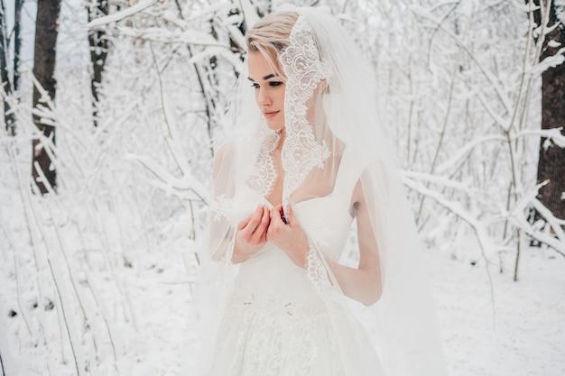 Невеста с позирует на открытом воздухе зимой