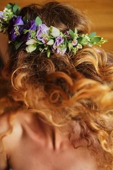 赤い髪と花のオレンジbeckgroundからの花輪を持つ花嫁