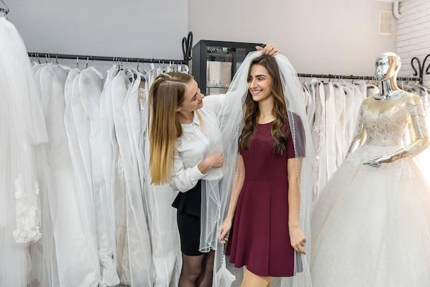店でウェディング ドレスを選ぶ仕立て屋の花嫁