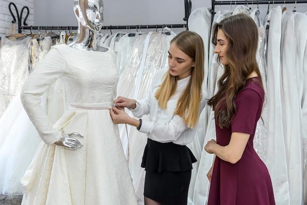 Невеста с портным, выбирая свадебное платье в магазине