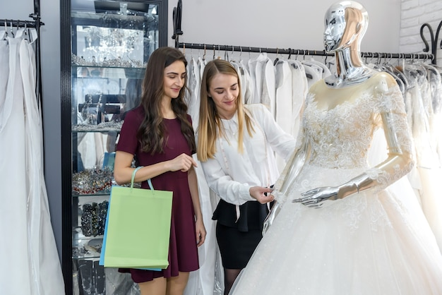 Bride with tailor choosing wedding dress in store