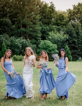 緑豊かな公園で楽しんでいる青いドレスに身を包んだ3人のブライドメイドの花嫁