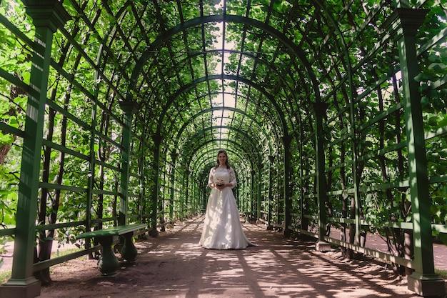 공원에서 녹색 잎 위에 손에 웨딩 부케와 신부. 맑은 결혼식에 웨딩 드레스에 예쁜 여자