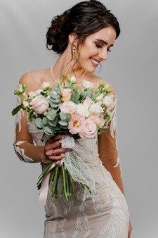 ウェディングブーケの花嫁は右側に見えて笑顔です。ソーシャルネットワークのための魅力的な女の子の縦の肖像画。空白の壁にウェディングドレスの女の子。
