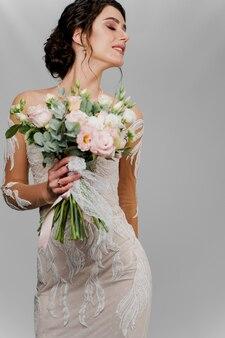ウェディングブーケの花嫁は右側に見えます。ソーシャルネットワークのための魅力的な女の子の縦の肖像画。空白の壁にウェディングドレスの女の子。