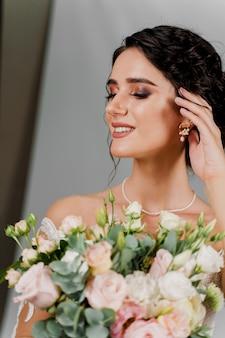 Невеста со свадебным букетом улыбается и касается ее лица и волос. портрет привлекательной девушки для социальных сетей. девушка в свадебном платье на глухой стене.