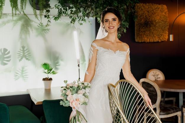Невеста со свадебным букетом улыбается. девушка в свадебном платье в роскошном ресторане.