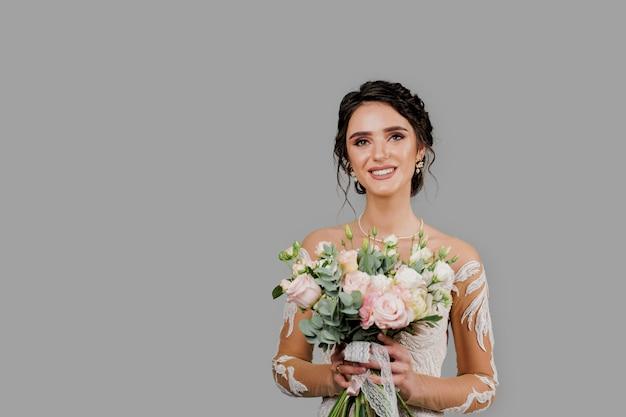 Невеста со свадебным букетом улыбается, смотрит в камеру и касается ее лица. портрет привлекательной девушки для социальных сетей. девушка в свадебном платье.