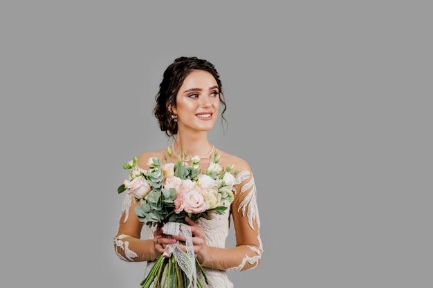 Невеста со свадебным букетом улыбается, смотрит вправо и касается ее лица. привлекательная девушка для социальных сетей. девушка в свадебном платье на глухой стене.