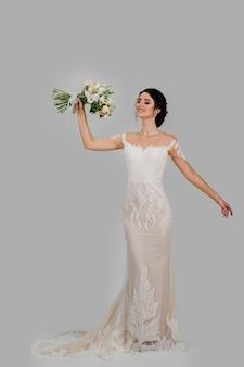 Невеста со свадебным букетом улыбается с закрытыми глазами.
