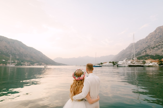 The bride in a wreath and groom hug on the pier near the old town of kotor in the bay of kotor