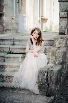 Bride.young fashion model with perfect skin and makeup, white background. beautiful bride on background white stairs. a woman in a long white dress is sitting on the stairs.