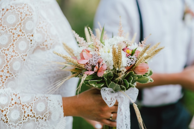 Bride young woman with the boho style bouquet with groom on wedding ceremony in forest