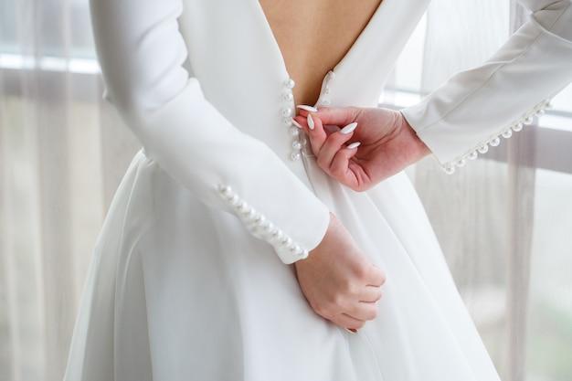 Bride zips zipper on her wedding white dress