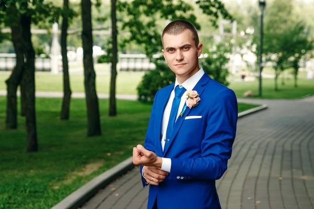 男は、緑の自然を背景にした古典的な青いスーツの花bride。結婚式、新郎、家族の作成。