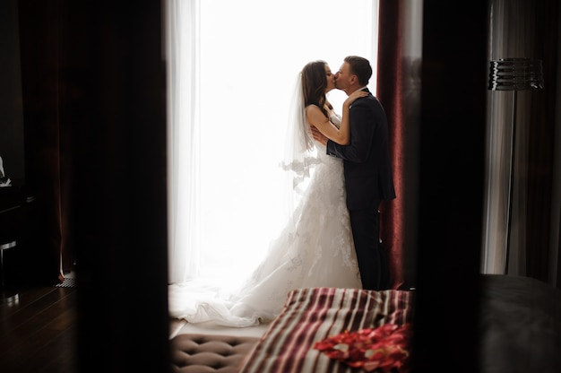 Bridegroom and bride in long dress are kissing near the window