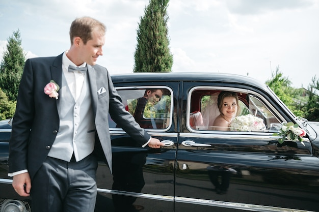 The bridegroom is standing by the car while the bride is in the car