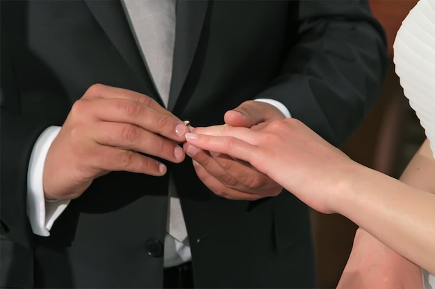 The bridegroom puts on an engagement ring on the finger of the bride