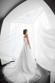 花嫁の美しさ。屋内でのウェディングドレスの若い女性