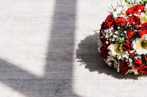 Букет невесты на винтажном деревянном полу в солнечном свете