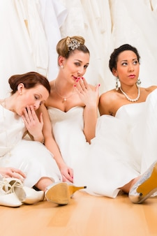 Brides drinking too much champagne in wedding shop