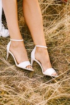 아름다운 highheeled 결혼식 신발에 신부 발은 건초에 누워