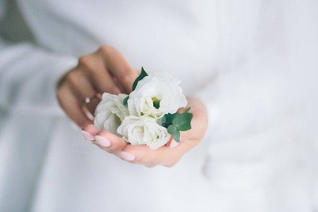 ブートニアを保持している花嫁の手。美しい白いドレスを着た女性。花嫁の準備。結婚式。