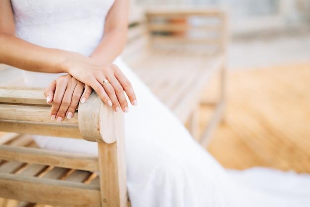 Руки невесты лежат на руке крупным планом деревянной скамейки
