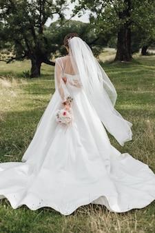 Невеста стоит в парке и держит за спиной свадебный букет без лица