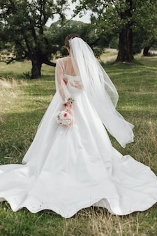 Brides stands in a park and holds a wedding bouquet behind her back, without face