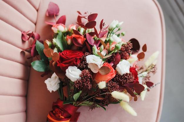 椅子にバラや他の花と花嫁のウェディングブーケ
