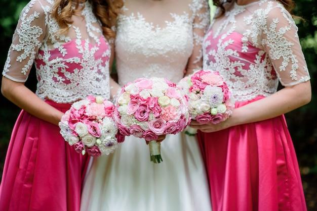 Bridesamaids в розовых платьях и невесте держат розовые свадебные букеты на руках