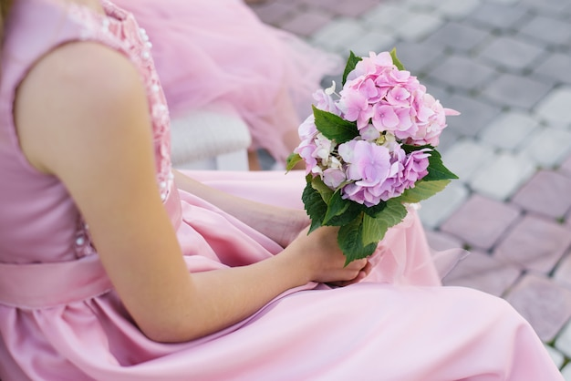Bridesmaid bouquet of pink hydrangea in the hands of a friend close up