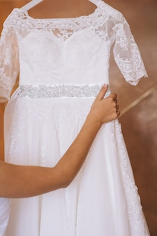 Bridesmaid buttoning the dress on bride, details of beautiful lace wedding dress