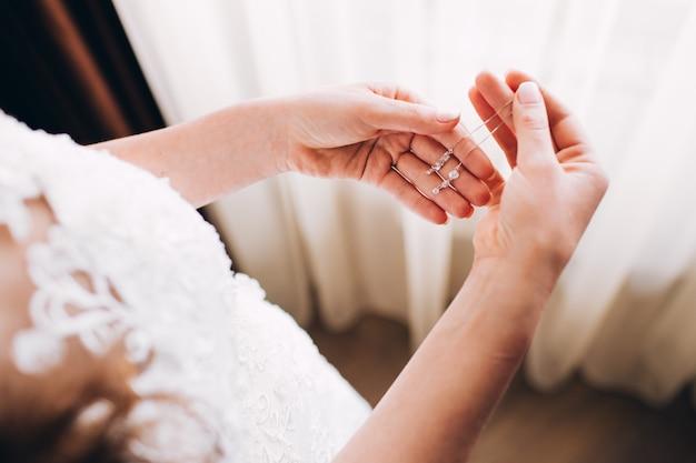 ウエディングドレスのイヤリング。女の子はイヤリングを保持しています。花嫁の優しい朝。ジュエリー広告