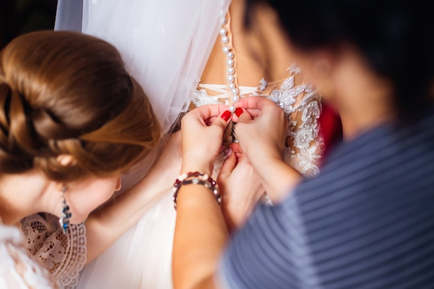 Bridesmaid fasten the buttons on the bride's dress.