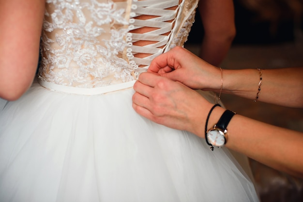 Bridesmaid hands fastens buttons on the back of the bride on the wedding white silk dress