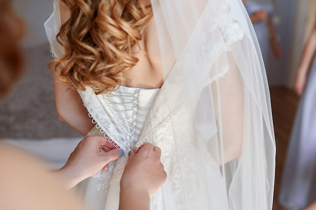 Bridesmaid help to dress a white bride dress