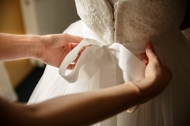 Bridesmaid help in fitting room for bride. wedding morning