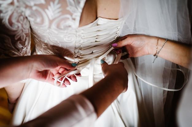花嫁介添人は花嫁がコルセットを固定し、彼女のドレスを取得するのを手伝います